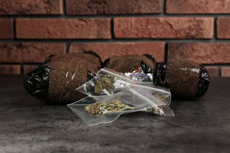 Hemp in packages on grey table. Drug addiction