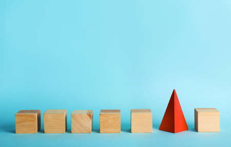 Row of wooden cubes and red pyramid on color background. Be different