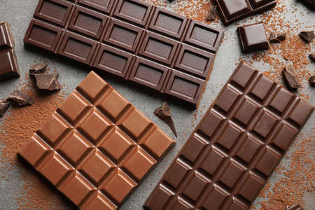 Different kinds of chocolate on grey background, top view