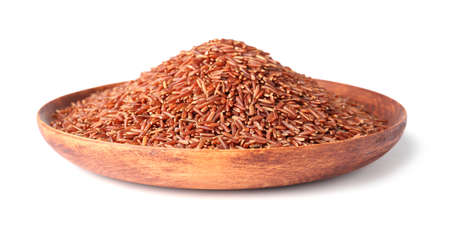 Plate with uncooked brown rice on white background