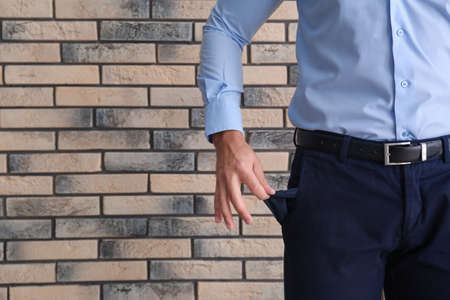 Businessman showing empty pocket near brick wall, closeup. Space for text