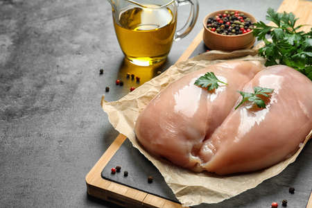 Wooden board with raw chicken breasts, pepper and parsley near olive oil in pitcher on table