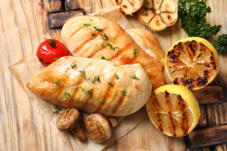 Grilled chicken breasts with garnish on wooden background, top view 写真素材