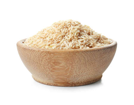Bowl with uncooked brown rice on white background
