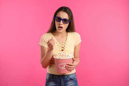 Emotional woman with 3D glasses and popcorn during cinema show on color background Stock Photo