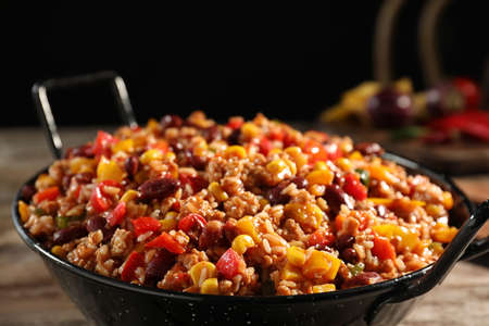 Pan with tasty chili con carne on wooden table, closeup