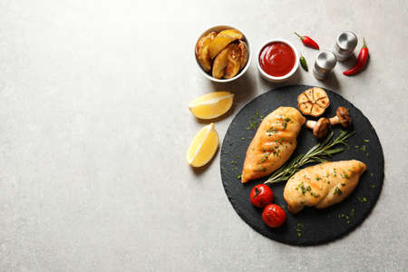 Fried chicken breasts served with sauce and garnish on grey background, flat lay. Space for text