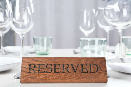 Table setting with RESERVED sign in restaurant Stock fotó
