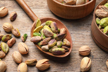 Composition with organic pistachio nuts on wooden table, closeup