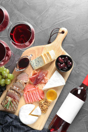 Flat lay composition with wine and snacks on grey background Фото со стока