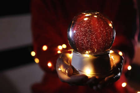 Woman holding snow globe and Christmas lights, closeup. Space for text