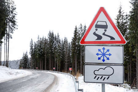 Warning traffic signs near snowy road through forest. Winter driving