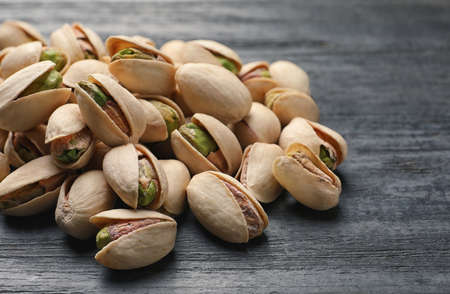 Heap of organic pistachio nuts on wooden table, closeup Imagens
