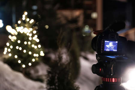 Photo of fir tree with Christmas lights on professional camera screen outdoors