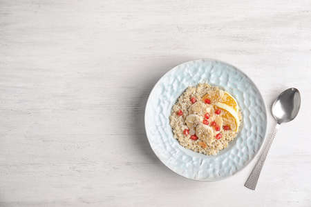 Plate of quinoa porridge with orange, banana and pomegranate seeds near spoon on white wooden background, top view. Space for text Stock Photo