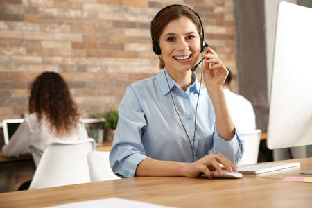 Technical support operator with headset at workplace
