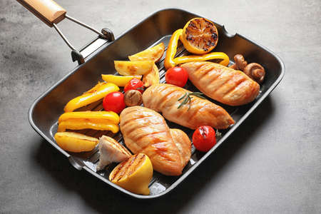 Grill pan with fried chicken breasts and garnish on grey background