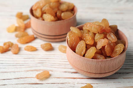Bowls with raisins on wooden table, space for text. Dried fruit as healthy snack