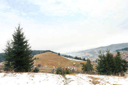Beautiful winter landscape with buildings and forest on hills Stock Photo