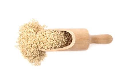 Scoop with uncooked brown rice on white background, top view Stock Photo