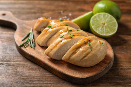 Wooden board with fried chicken breast and limes on table, closeup Stock Photo