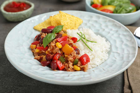 Tasty chili con carne served with rice on gray table