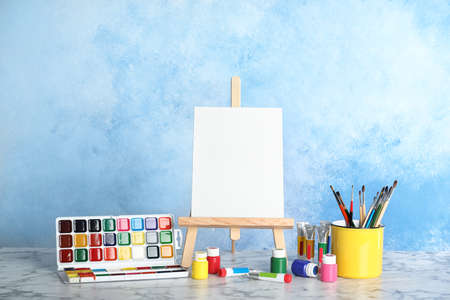 Cavalletto in legno con tavola di tela bianca e strumenti di pittura per bambini sul tavolo vicino alla parete colorata