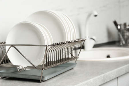 Rejilla de secado con platos limpios en la encimera de la cocina. Espacio para texto