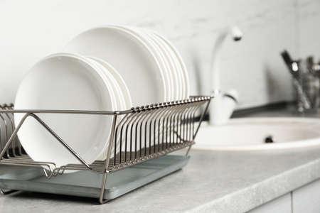 Suszarka z czystymi naczyniami na blacie kuchennym. Miejsce na tekst