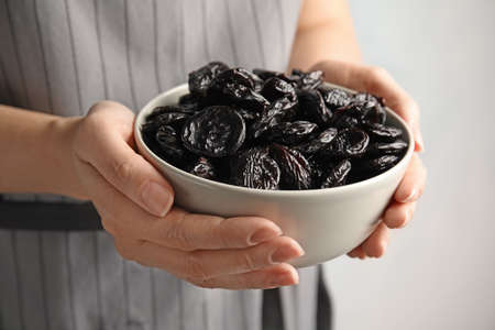 Woman holding bowl of dried plums, closeup. Healthy fruit Stock Photo