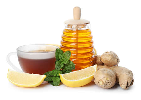 Jar with honey, cup of tea, ginger, mint and lemon on white background. Cough remedies