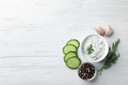 Tzatziki sauce in bowl with slices of cucumber, garlic, pepper and dill on white wooden background, top view. Space for text