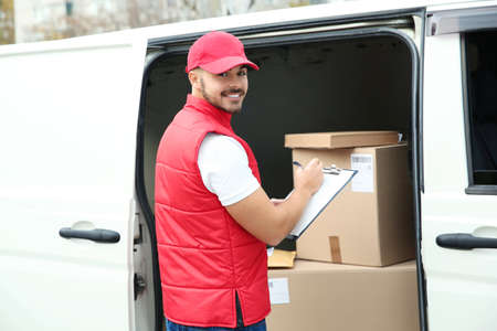 Young courier checking amount of parcels in delivery van, outdoors Banque d'images - 115565573