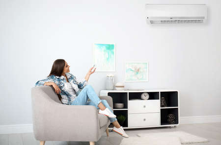 Young woman turning on air conditioner at home