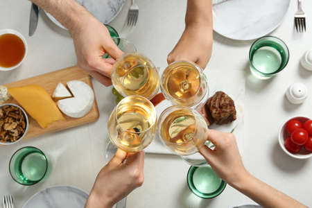 People holding glasses of white wine over table with tasty snacks, top view