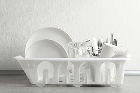 Drying rack with clean dishes and cutlery on table near light wall