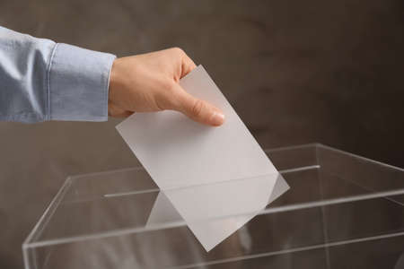 Man putting his vote into ballot box on color background, closeup