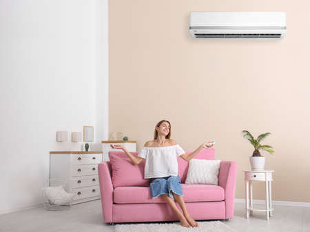 Mujer joven relajante cerca del aire acondicionado en casa Foto de archivo
