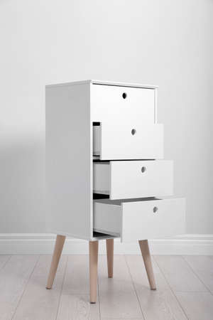 Stylish chest of drawers near white wall. Furniture for wardrobe room Stock Photo