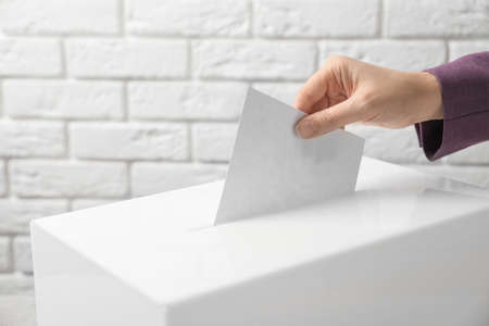 Woman putting her vote into ballot box against brick wall, closeup Stock Photo