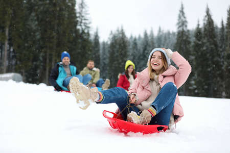 Heureux amis glissant sur des traîneaux à l'extérieur. Vacances d'hiver
