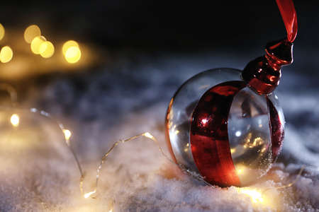 Christmas ball and fairy lights on white snow outdoors. Space for text