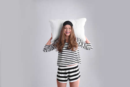 Happy woman in pajamas with pillow on gray background