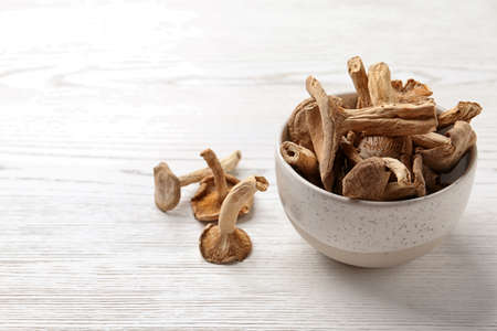 Bowl of dried mushrooms on wooden background. Space for text