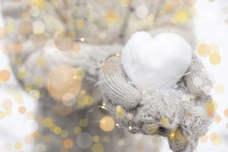 Woman holding Christmas lights and heart made of snow, closeup Stock Photo