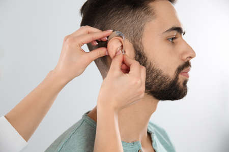 Otolaryngologist putting hearing aid in man's ear on white background Banco de Imagens