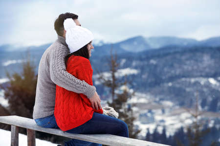 Couple sitting on bench and enjoying mountain landscape, space for text. Winter vacation Banque d'images