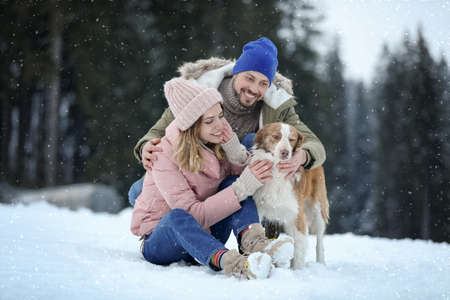 Cute couple with dog near forest. Winter vacation Stock Photo