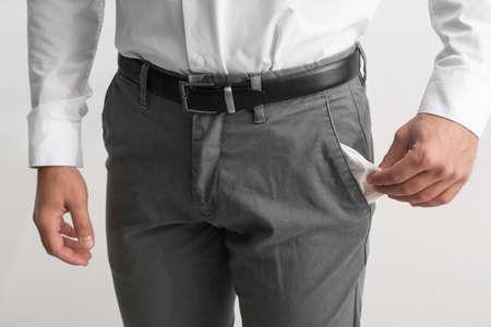 Businessman showing empty pocket on light background, closeup Banco de Imagens