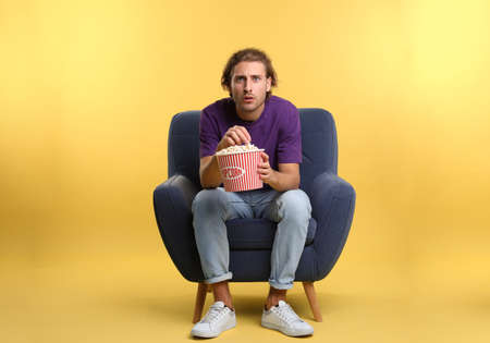 Emotional man with popcorn sitting in armchair during cinema show on color background Stock fotó